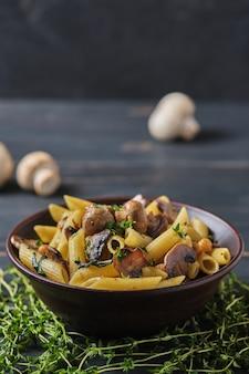 Makaron wegetariański z pieczarkami, ciecierzycą, szpinakiem, przyprawami i ziołami. włoski makaron w misce na starym drewnianym stole.
