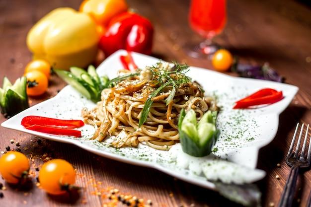 Makaron widok z boku z warzywami, ogórkiem kukurydzianym i papryką