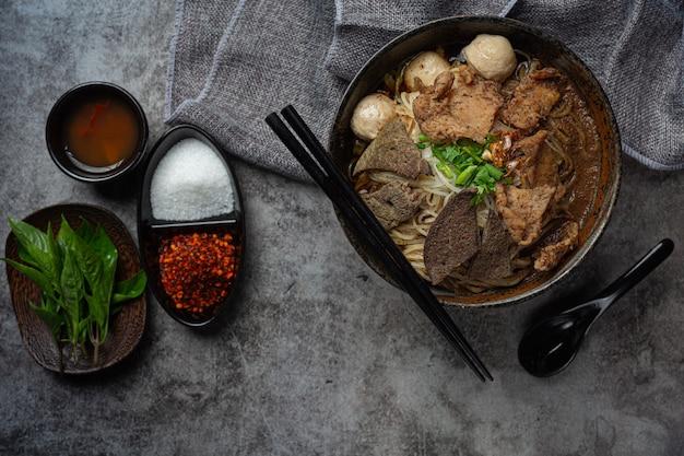 Makaron wieprzowy z łodzi, klasyczne tajskie jedzenie i popularne menu oraz gotowe do spożycia zupy. w misce jest też bazylia.