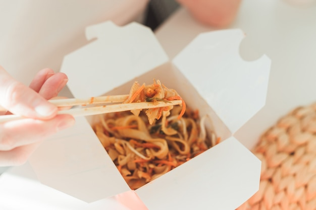 Makaron wok w pudełku na wynos. kobieta jedzenie pałeczkami, bliska widok na kobiece dłonie. chińskie tradycyjne potrawy z warzywami i owocami morza.