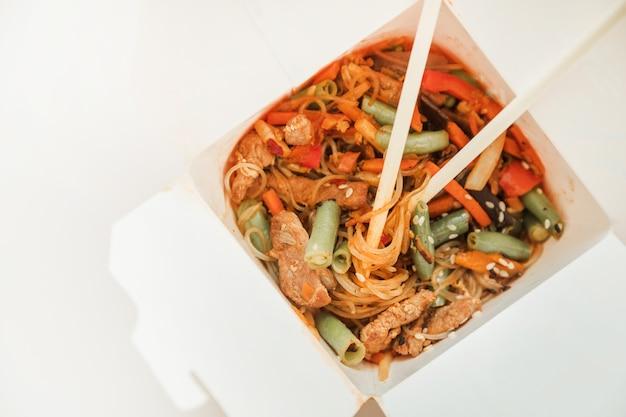 Makaron wok w pudełku na wynos. makaron pszenny z kaczką po pekińsku i warzywami. tradycyjna kuchnia chińska.