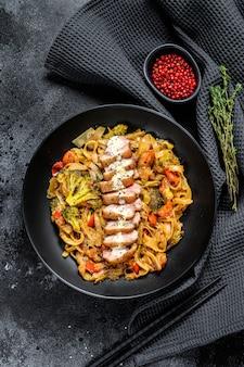 Makaron wok z mięsem z kaczki i warzywami. czarne tło.