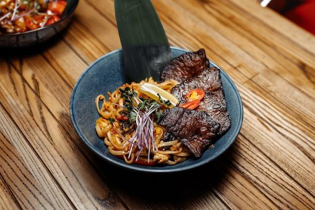 Makaron z cielęciną i warzywami na szarym stole.
