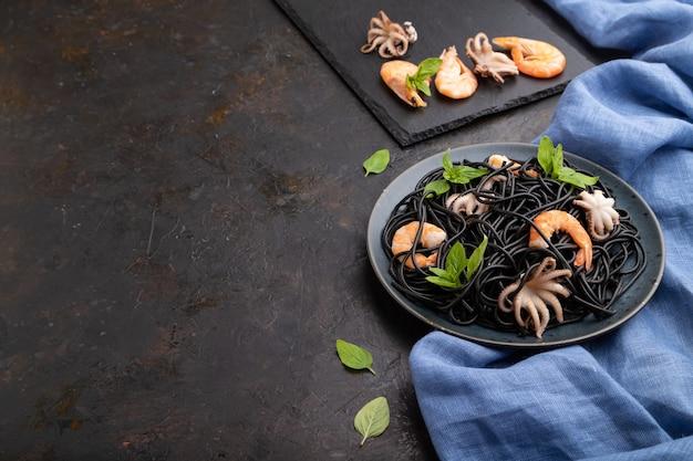 Makaron z czarnym atramentem mątwy z krewetkami lub krewetkami i małymi ośmiornicami na czarnym betonowym tle i niebieską tkaniną. widok z boku, miejsce na kopię.