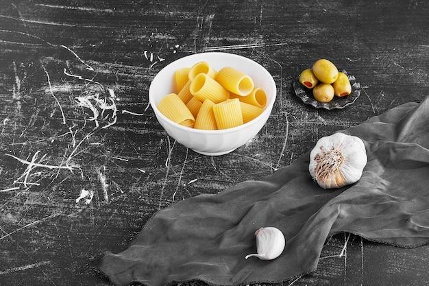Makaron z czosnkiem i oliwkami w ceramicznej misce.