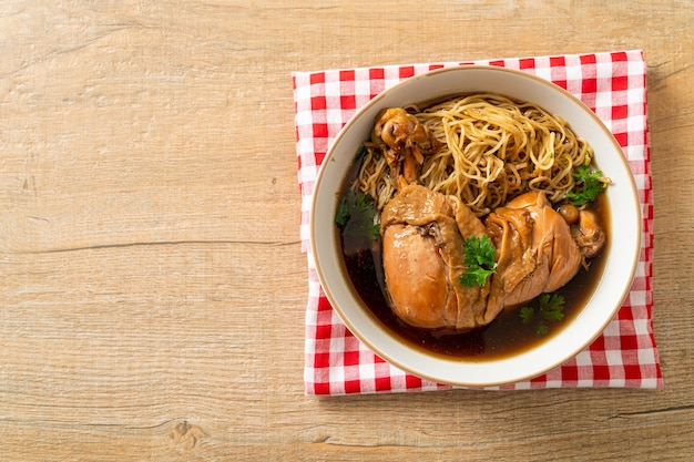 Makaron z duszonym kurczakiem w brązowej misce zupy - po azjatyckim stylu