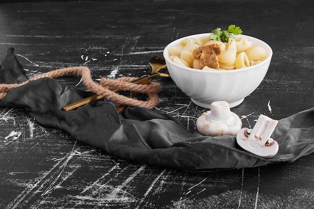 Makaron z grzybami w ceramicznej misce.