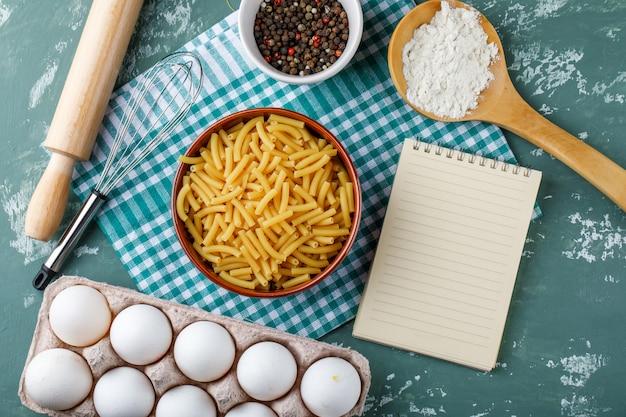 Makaron z jajkami, wałkiem do ciasta, trzepaczką, pieprzem, skrobią i zeszytem