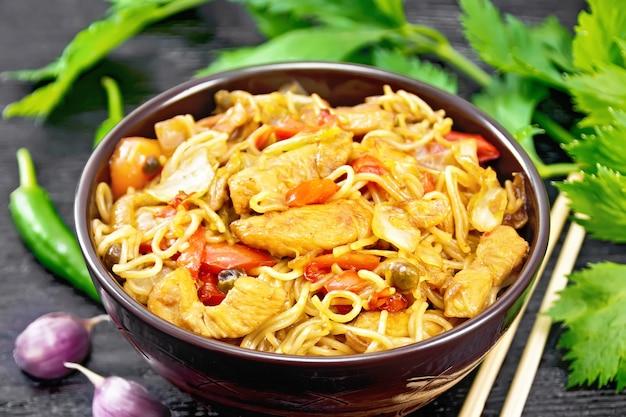 Makaron z kapustą, piersią z kurczaka, słodką czerwoną papryką, cebulą i groszkiem doprawiony sosem sojowym w misce, czosnkiem i zielonymi liśćmi selera na ciemnym tle drewnianej deski