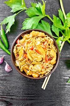 Makaron z kapustą, piersią z kurczaka, słodką czerwoną papryką, cebulą i groszkiem doprawiony sosem sojowym w misce, czosnkiem i zielonymi liśćmi selera na tle drewnianej deski z góry