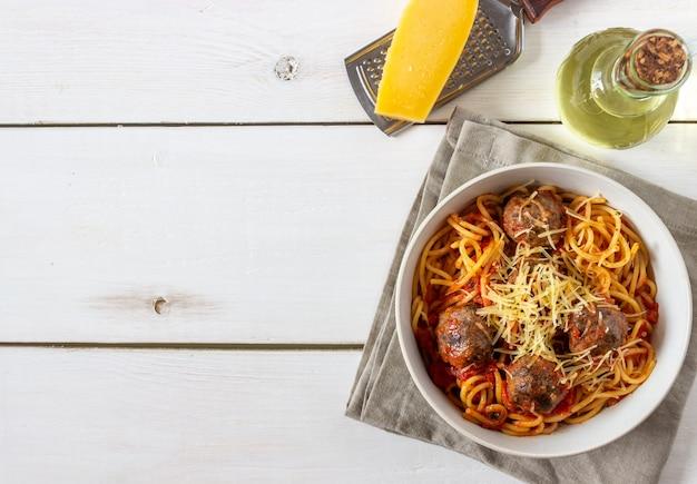 Makaron z klopsikami i sosem pomidorowym na drewnianym tle.
