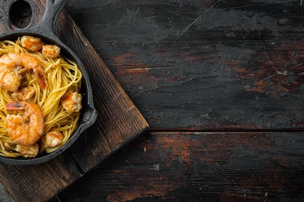 Makaron z krewetkami i sosem pesto, na żeliwnej patelni, na starym ciemnym drewnianym stole, płaski widok z góry, z miejscem na kopię na tekst