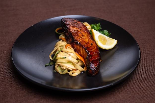 Makaron z łososiem w sosie sojowym i cytryną na czarnym talerzu.