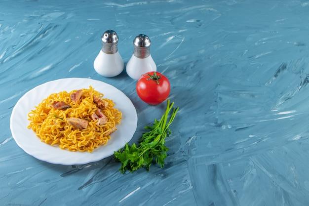 Makaron z mięsem na talerzu obok pęczka pietruszki, pomidorów i soli, na marmurowym tle.