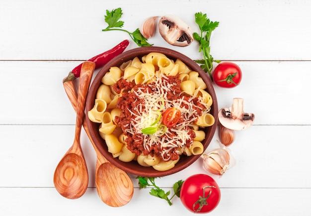 Makaron z mięsem, sosem pomidorowym i warzywami na stole