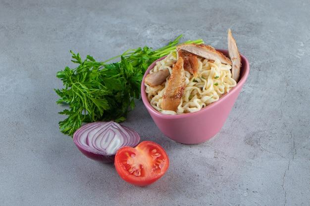 Makaron z mięsem w misce obok pęczka pietruszki, pomidorów i cebuli, na marmurowej powierzchni.