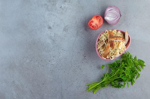 Makaron z mięsem w misce obok pęczka pietruszki, pomidorów i cebuli, na marmurowym tle.