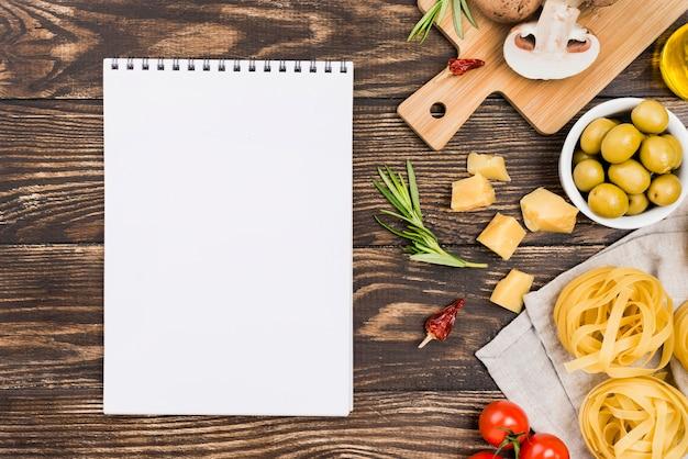 Makaron z oliwkami i warzywami obok notesu