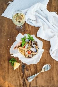 Makaron z owocami morza. spaghetti z małżami i krewetkami w misce, kieliszek białego wina na rustykalnym drewnianym stole