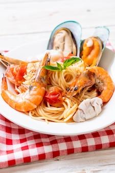 Makaron z owocami morza spaghetti z małżami, krewetkami, squis, małżami i pomidorami