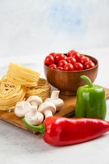 Makaron z pieczarkami, papryczką chili i pomidorkami koktajlowymi na drewnianej desce.