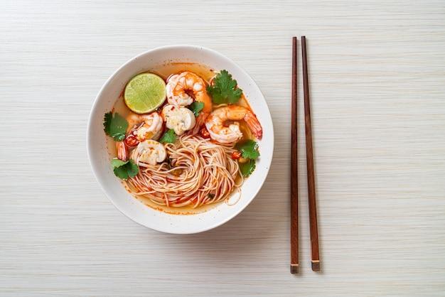 Makaron z pikantną zupą i krewetkami w białej misce (tom yum kung). azjatycki styl żywności