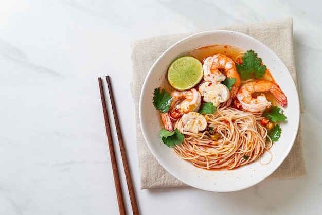 Makaron z pikantną zupą i krewetkami w białej misce (tom yum kung) - kuchnia azjatycka
