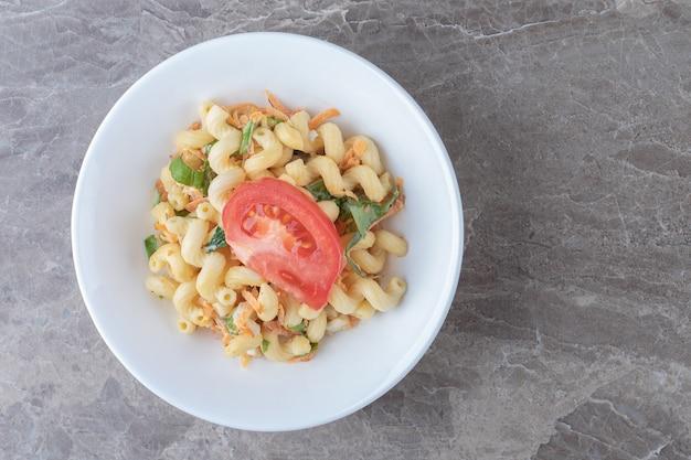 Makaron z pokrojonymi w kostkę warzywami na białym talerzu.