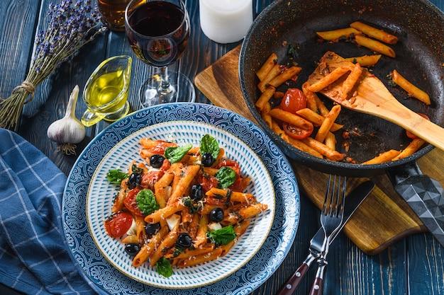 Makaron z pomidorkami koktajlowymi, mozzarellą i oliwkami szpinakowymi, winem i oliwą na drewnianym stole. styl rustykalny.