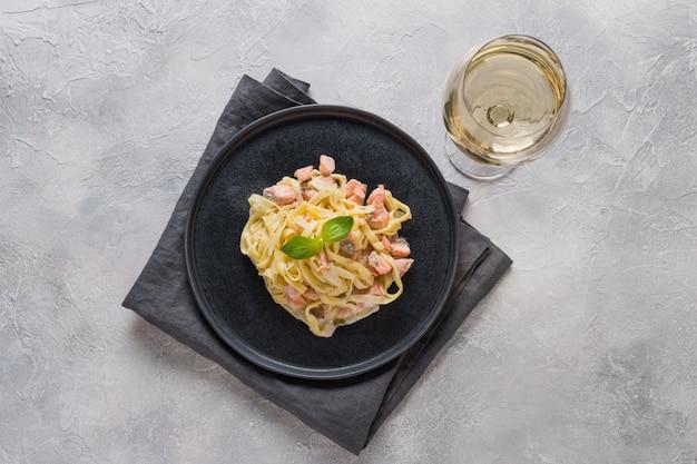 Makaron z pstrągiem w ciemnym talerzu i kieliszek białego wina.