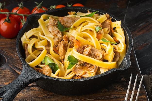Makaron z rozmarynem na gulaszu z królika, smażony na żeliwnej patelni lub garnku, na starym ciemnym drewnianym stole