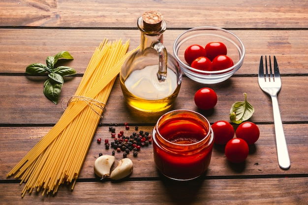 Makaron z różnymi składnikami do gotowania włoskiego jedzenia, na rustykalnym drewnianym stole