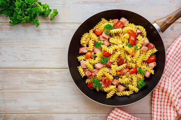 Makaron z semoliny z pszenicy durum z pomidorem, groszkiem na patelni. widok z góry.