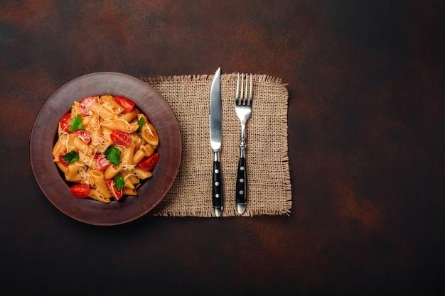Makaron z serem, czereśniowym pomidorem, rozwidleniem i nożem na ośniedziałym tle.