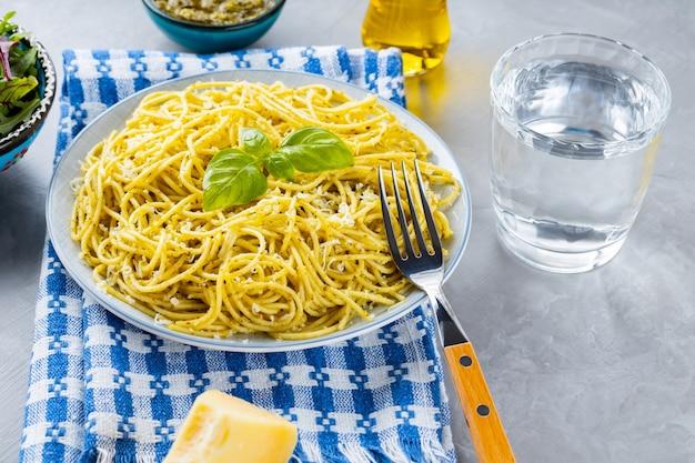 Makaron z sosem pesto i dodatkami. spaghetti z sosem pesto i bazylią na szarym tle. tradycyjna kuchnia włoska. stylizacja żywności