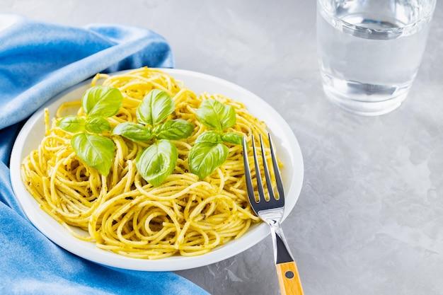 Makaron z sosem pesto i listkami bazylii. spaghetti z sosem pesto i świeżą bazylią na szarym tle. kuchnia włoska. stylizacja żywności