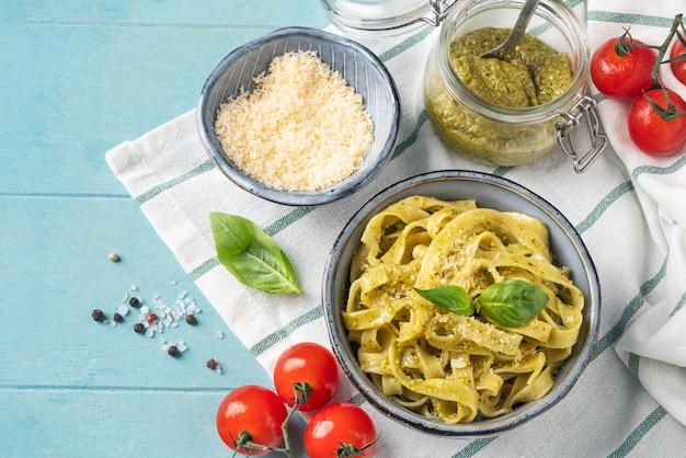 Makaron z sosem pesto, koncepcja gotowania, składników i przypraw na stole z naczyniem. widok z góry