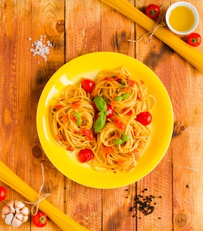 Makaron z sosem pomidorowym i innymi składnikami na drewnianym tle wolnego miejsca na tekst.