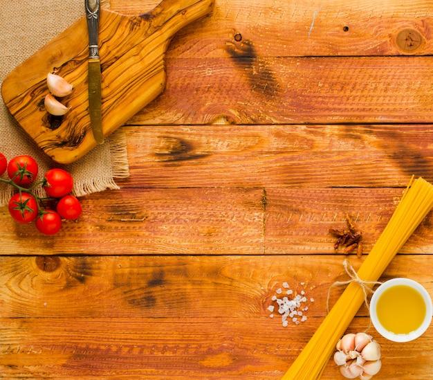 Makaron z sosem pomidorowym i innymi składnikami na drewnianym tle