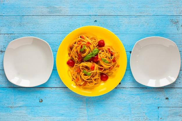 Makaron z sosem pomidorowym i innymi składnikami na jasnoniebieskim drewnie