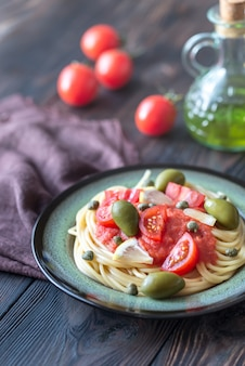 Makaron z sosem pomidorowym, oliwkami i kaparami na talerzu