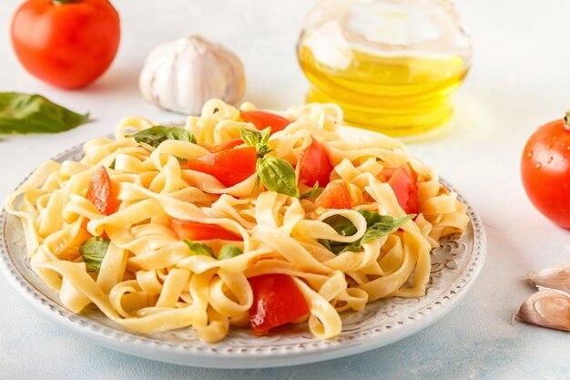 Makaron z sosem pomidorowym podawany z bazylią, selektywne focus.
