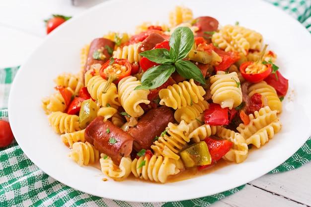 Makaron z sosem pomidorowym z kiełbasą, pomidorami, zieloną bazylią ozdobiony białym talerzem na drewnianym stole.