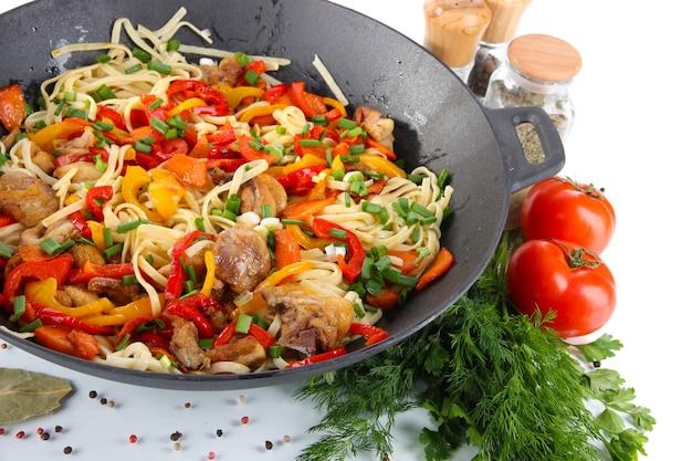 Makaron z warzywami na woku na białym tle