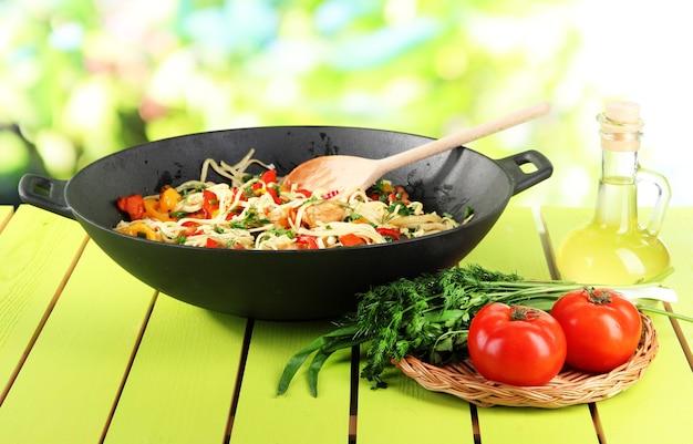 Makaron z warzywami na woku na rozmytej zieleni