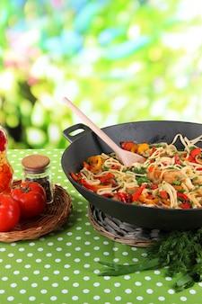 Makaron z warzywami na woku na tle przyrody