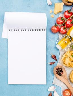 Makaron z warzywami obok notesu