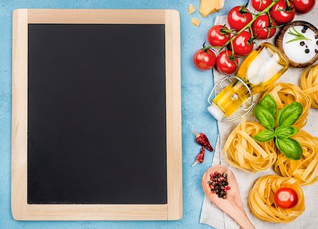 Makaron z warzywami obok tablicy