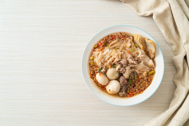Makaron z wieprzowiną i klopsikami w pikantnej zupie lub makaron tom yum w azjatyckim stylu