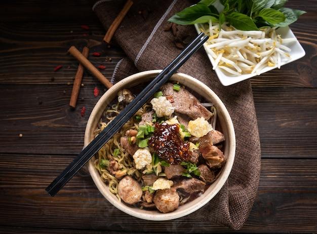 Makaron z wieprzowiną i kulkami wieprzowymi, pasta chilli z zupą po tajsku i warzywami. makaron łódka. selektywne skupienie. widok z góry